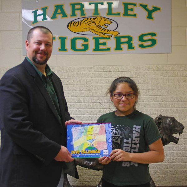 Principal Kurt Koepke presents Christy Hernandez Zamarrippa with the 2018 NPGCD Water Conservation Calendar with her artwork showcased on the cover.